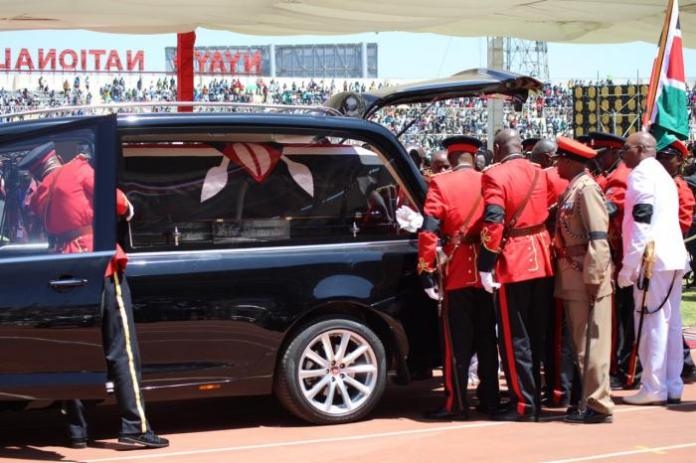Officers place the late President Daniel arap Moi's body in a Jaguar XJ limousine on February 11 at Nyayo National Stadium.