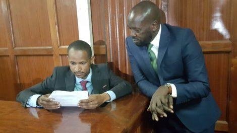 Embakasi East MP Babu Owino peruses court documents in the company of his lawyer Cliff Ombeta when he appeared before the Millimani Law Courts on January 27