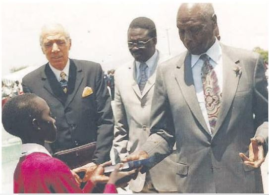 Jayne Chelimo (pictured) receiving a cheque from the late second president of the Republic of Kenya Daniel Torotich Arap Moi