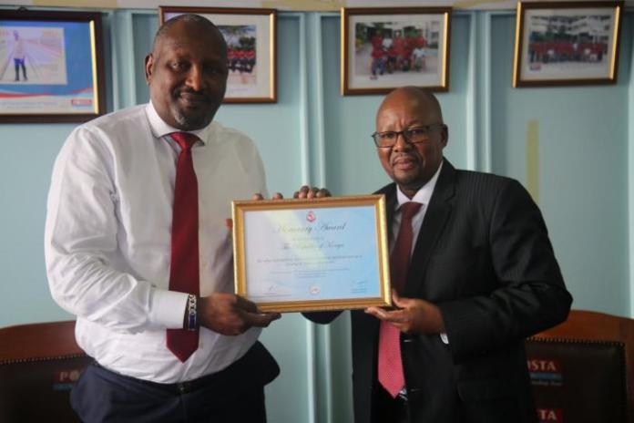 The Postmaster General Mr. Dan Kagwe presents an Honorary award to Postal Corporation of Kenya chairman Nick Salat
