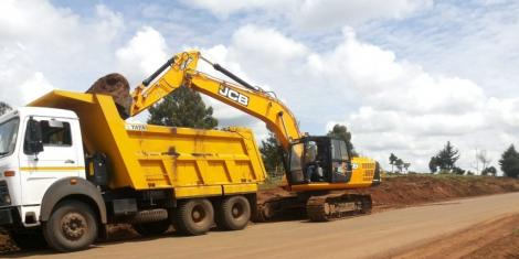 A truck and an excavator during a road construction project.