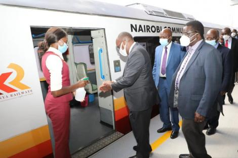Transport CS James Macharia (second left) sanitises his hands while preparing to board a train on Monday, December 7, 2020.