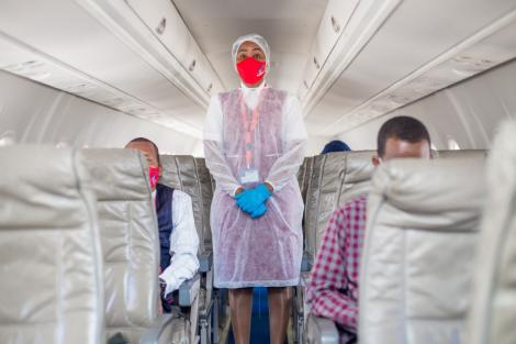 A healthworker on a plan preparing for takeoff.
