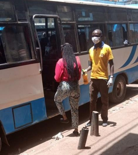 A tout stands watch at the matatu doors armed with a hand sanitizer, sterile gloves and a mask.