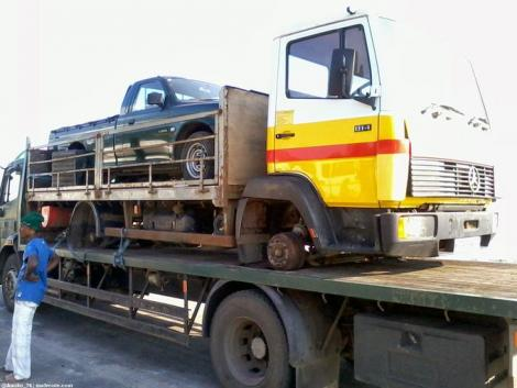 A truck transporting another truck loaded with a pick-up truck.