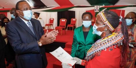 President Uhuru Kenyatta issuing title deeds at the Kenyatta International Convention Centre