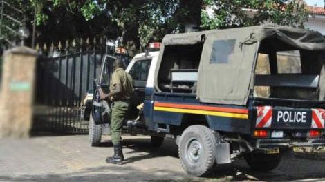 An armed Kenya police officer steps out of a police car.