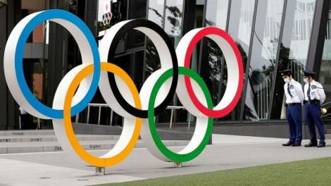 Guards stand next to a logo signifying the olympics