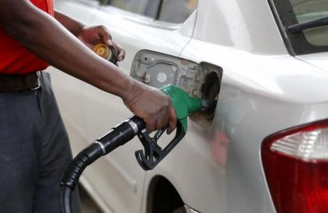 A petrol station attendant pumping fuel into a car.