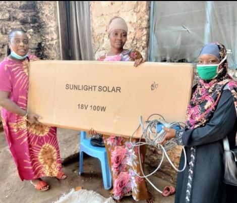 Diana Chitsaka Mwangala, a team leader and founder of Gift A Girl Child Initiative, presents a solar light to the mother of Salim Khamisi.