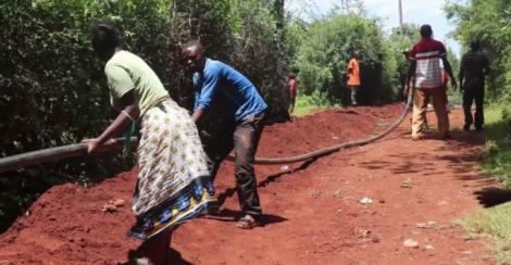Residents of two villages in Kandara Sub County dig trenches for a government project