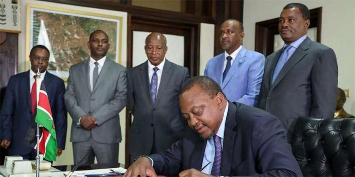 President Uhuru Kenyatta signs the Finance Bill 2019 into law at State House Nairobi on November 8, 2019. Looking on are House Speaker Justin Muturi, Majority Leader Aden Duale, Attorney-General Paul Kihara, acting Treasury Secretary Ukur Yatani and Treasury PS Julius Muia.