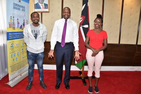 Brain Orinda (left), Health Cabinet Secretary Mutahi Kagwe (centre) Brenda Cherotich (right) posing for a photo at Afya House on April Wednesday 1, 2020.