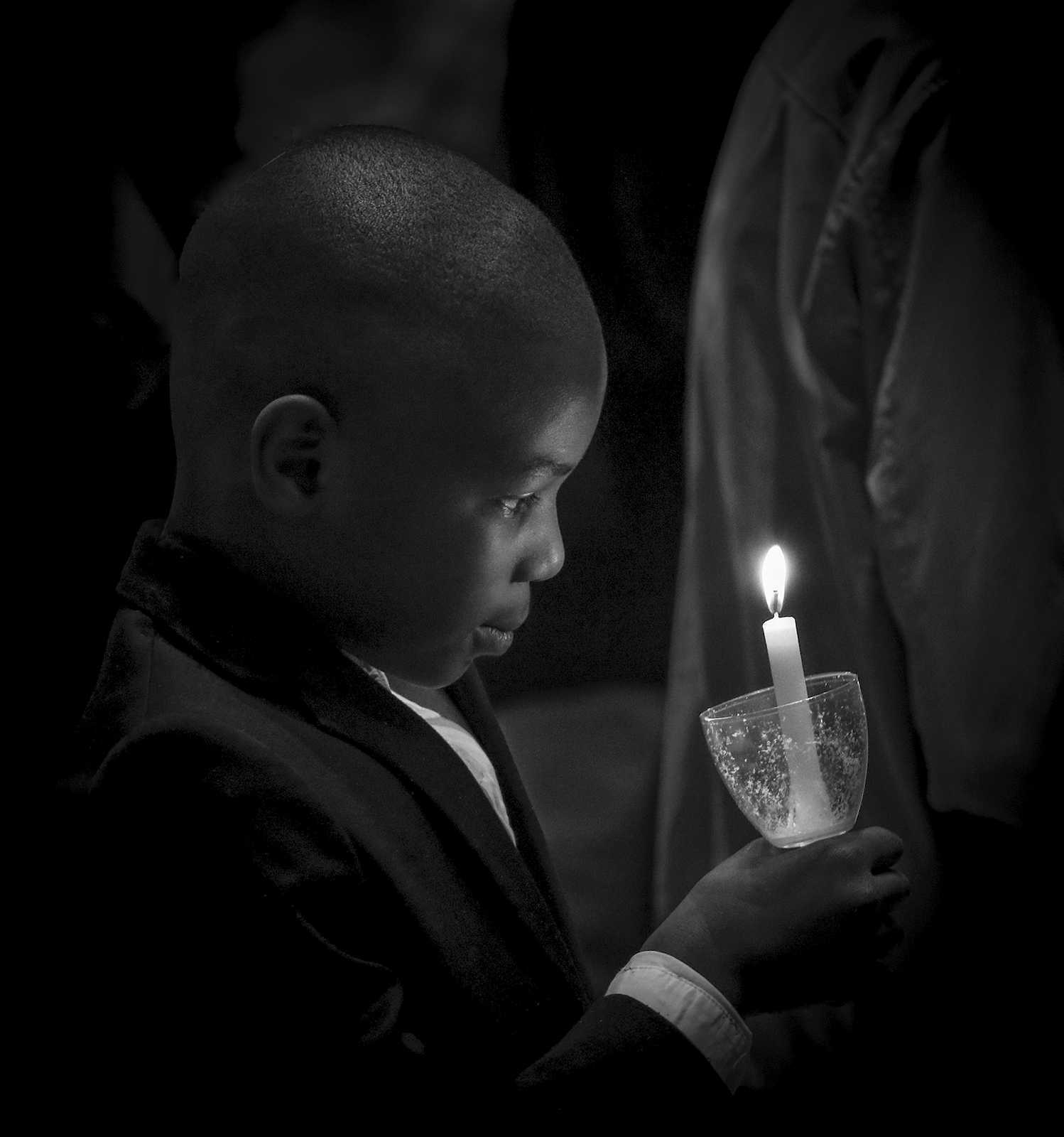 Young Boy Carrying Candle at Easter Ceremony