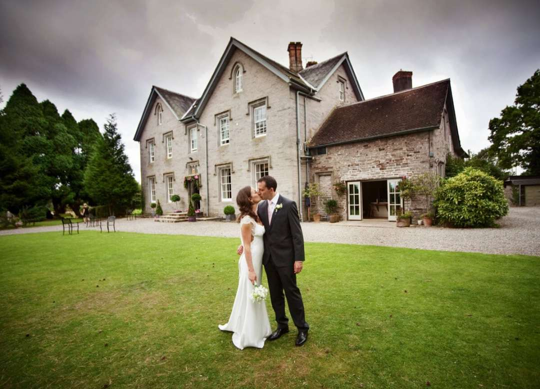 Bride and groom kissing in front of Lemore Manor in Herefordshire