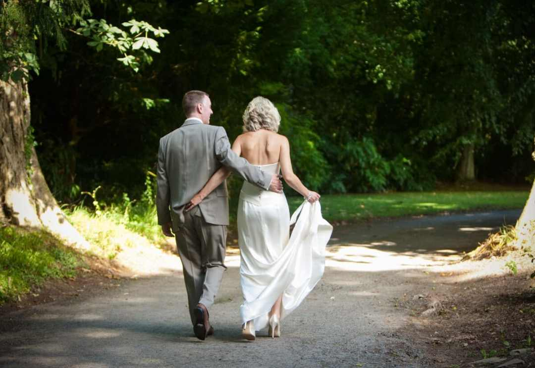 Bride and groom walking down country lane at Lemore Manor weddings