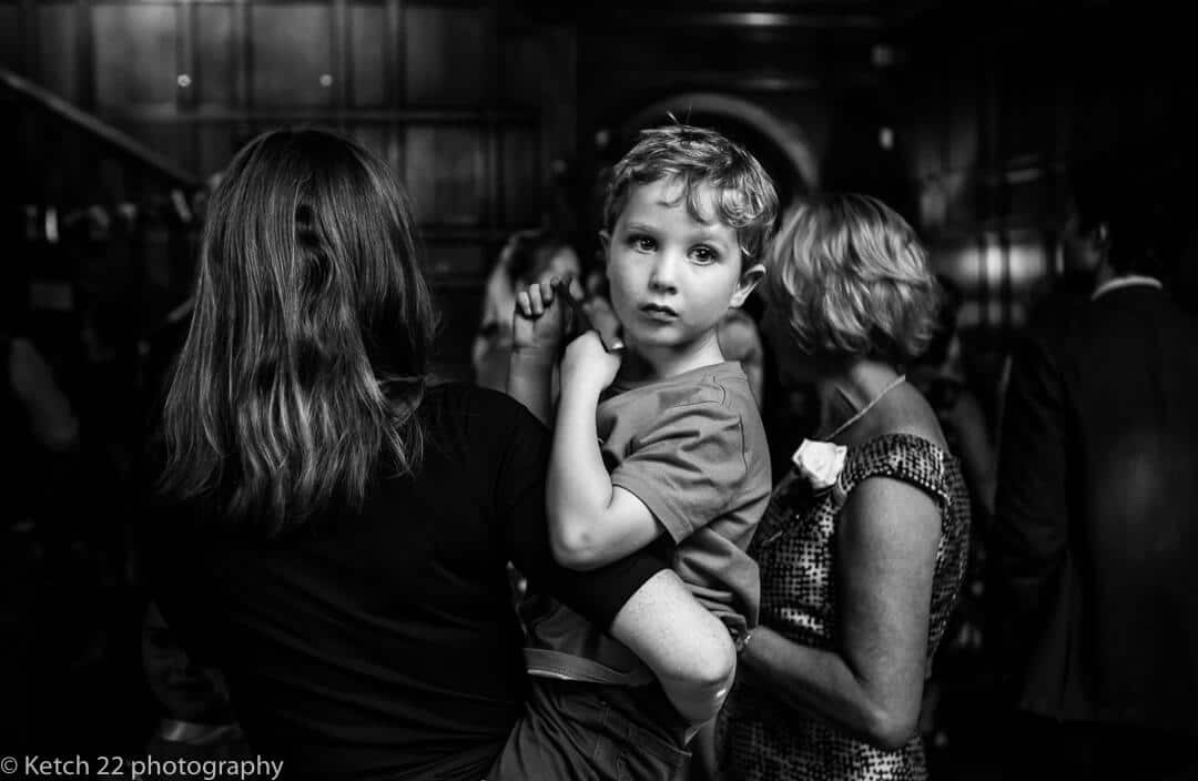 Black and white portrait of young boy at wedding reception