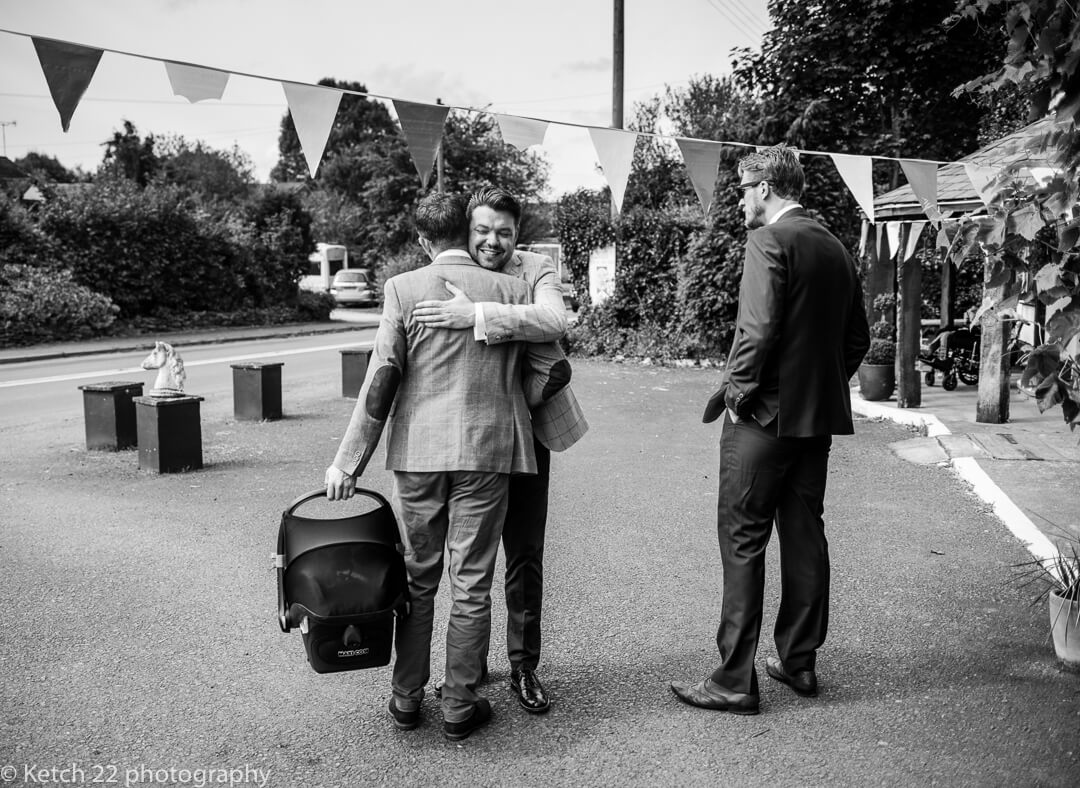 Groom greeting one of his ushers at documentary wedding