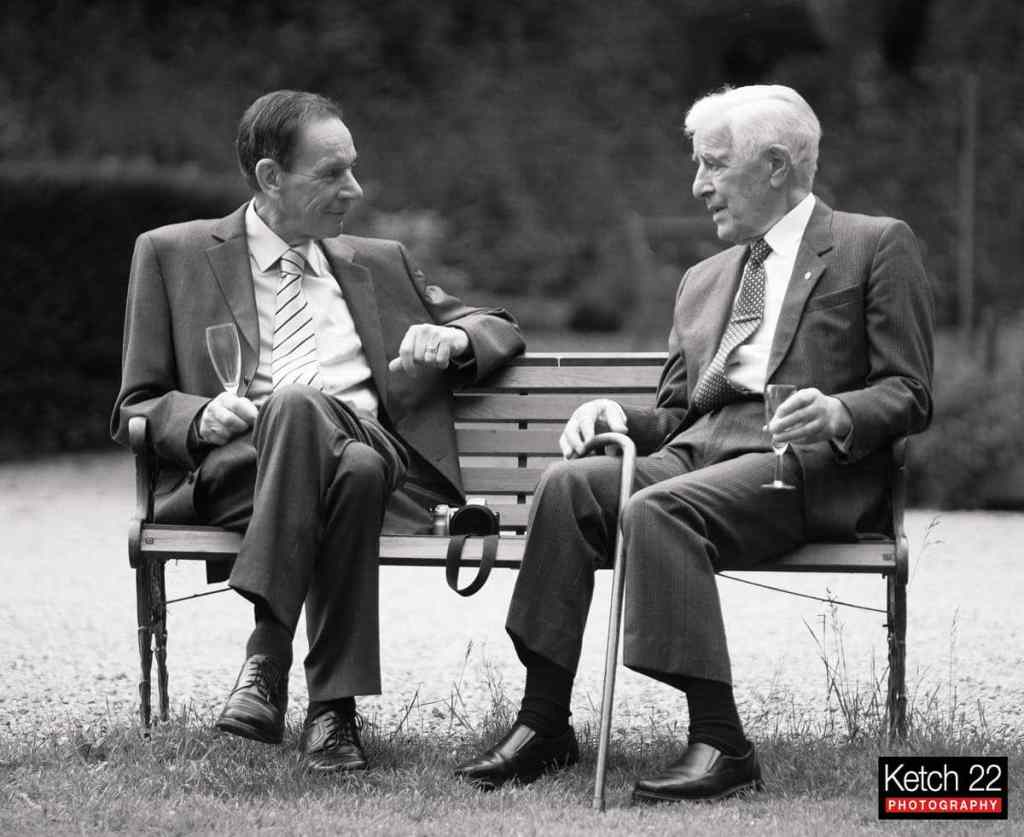 Two grandads chatting sat on bench at Parkfields country house wedding