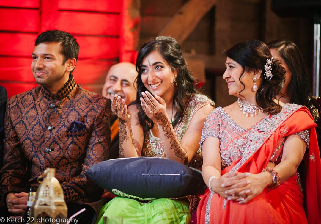 Bride groom and Mum watching dancers at Indian wedding in London