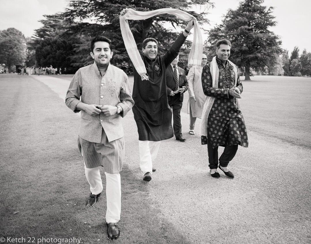 Weddiing guests cheering and waving scarf at Indian wedding