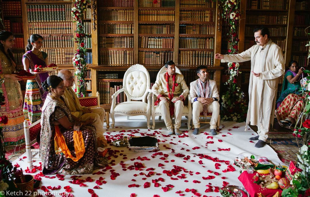 Groom and best man having blessing at Indian wedding ceremony at Highclere