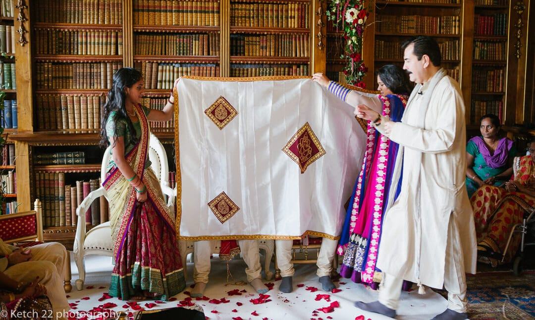 Groom is hidden by white sheet at Hindu wedding ceremony