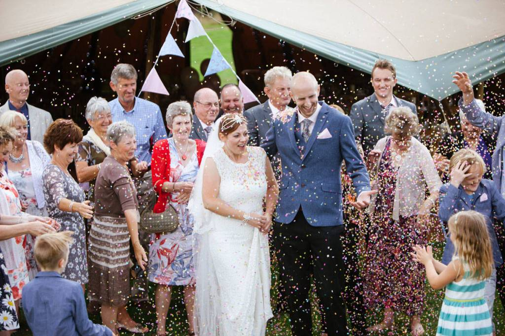 Wedding guests throwing confetti on bride and groom in Shropshire