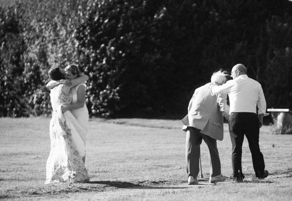 Bride hugging best friend while Grandad leaves at wedding in Shropshire