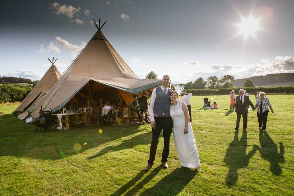 Portrait of bride and groom in evening sun light outside marquee at wedding in Shropshire