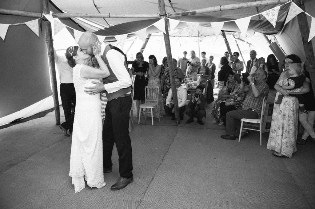 Bride kissing groom at wedding ceremony in vintage tent shropshire