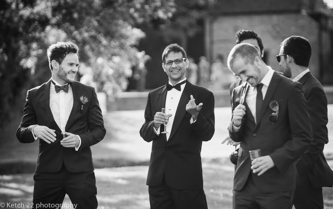 Wedding guests in tuxedo's laughing at Hindu wedding reception