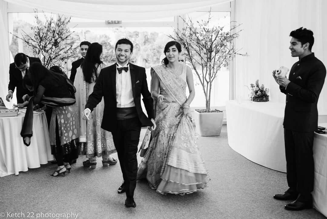 Bride and groom enter marquee at Indian wedding reception