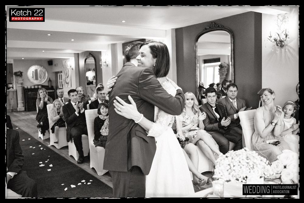 Bride and groom hugging at wedding ceremony at The Old Lodge Minchampton