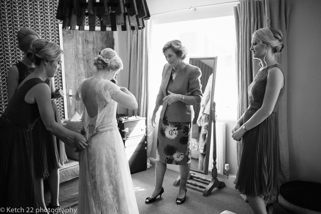 Bride putting on dress at wedding preparations