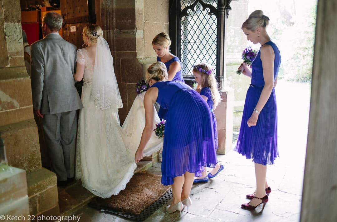 Bridesmaids adjusting brides dress before to walks into church for wedding ceremony