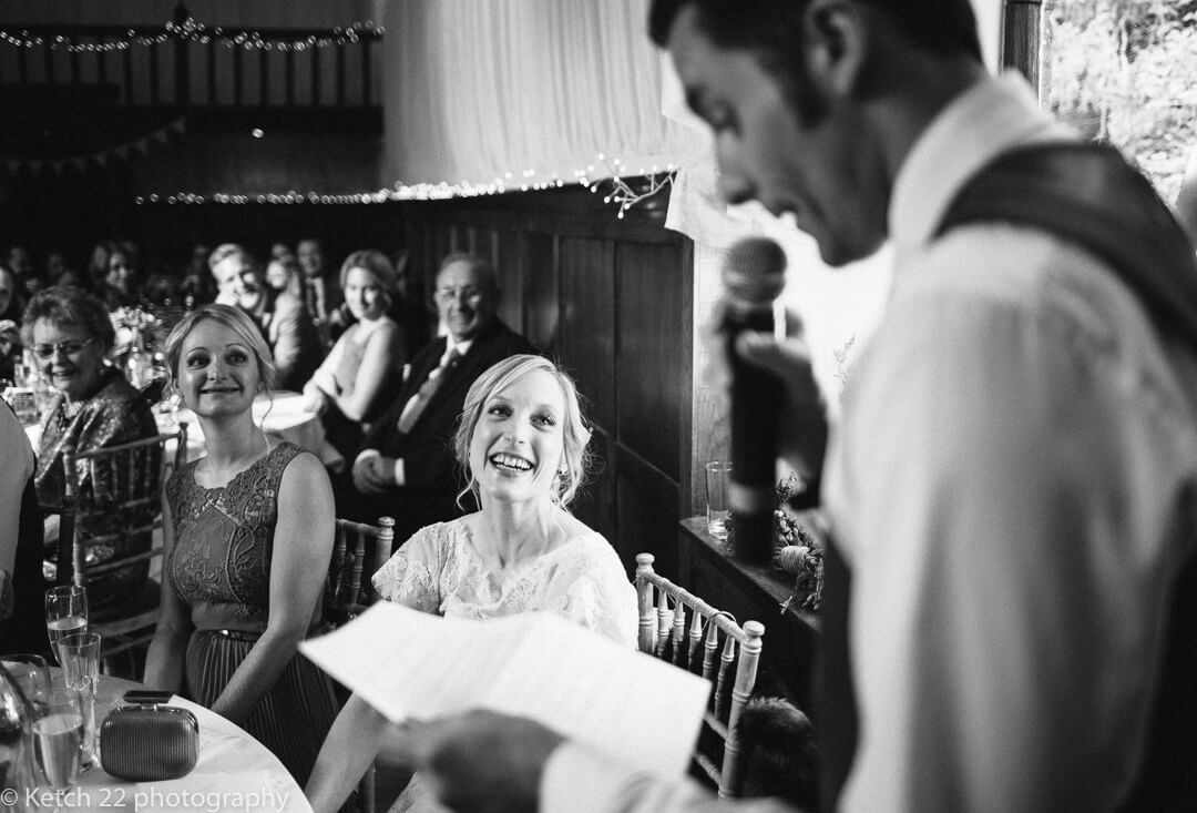 Bride smiling looking at groom whilst he makes wedding speech in Herefordshire