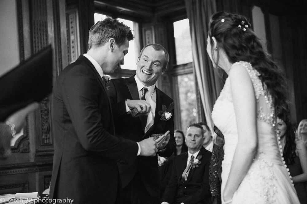 Best man handing ring to groom at The manor by the lake gloucestershire
