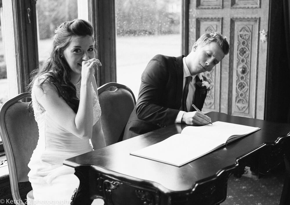 Signing the registrar at Manor by the lake wedding Gloucestershire