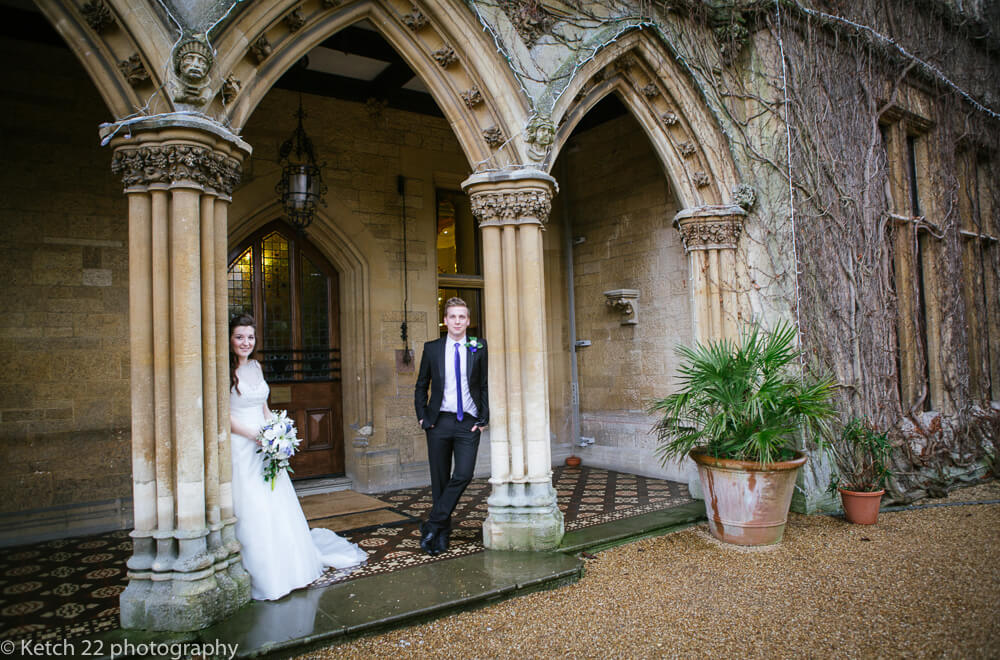 Bride and groom leaning on pillars at Manor by the lake wedding Cheltenham