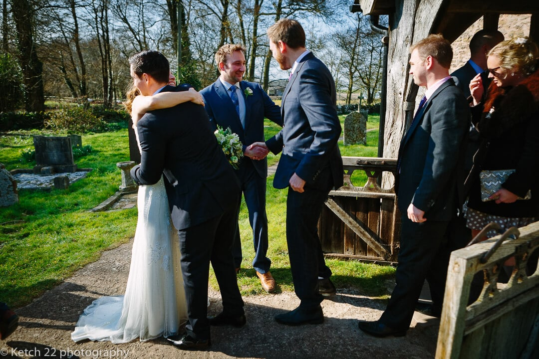 Bride and groom greet wedding guest outside church