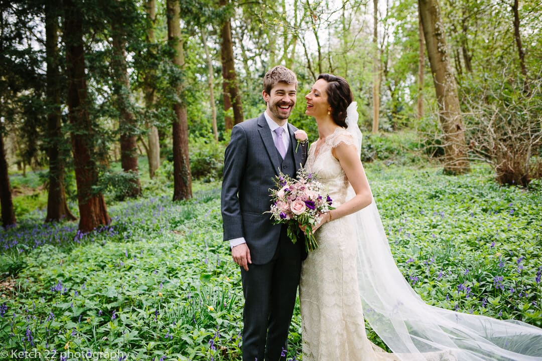 Portrait of bride and groom laughing in the gardens at Spring wedding