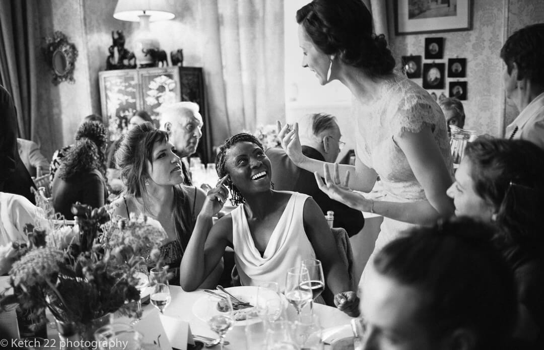 Expressive bride talking to wedding guests during dinner