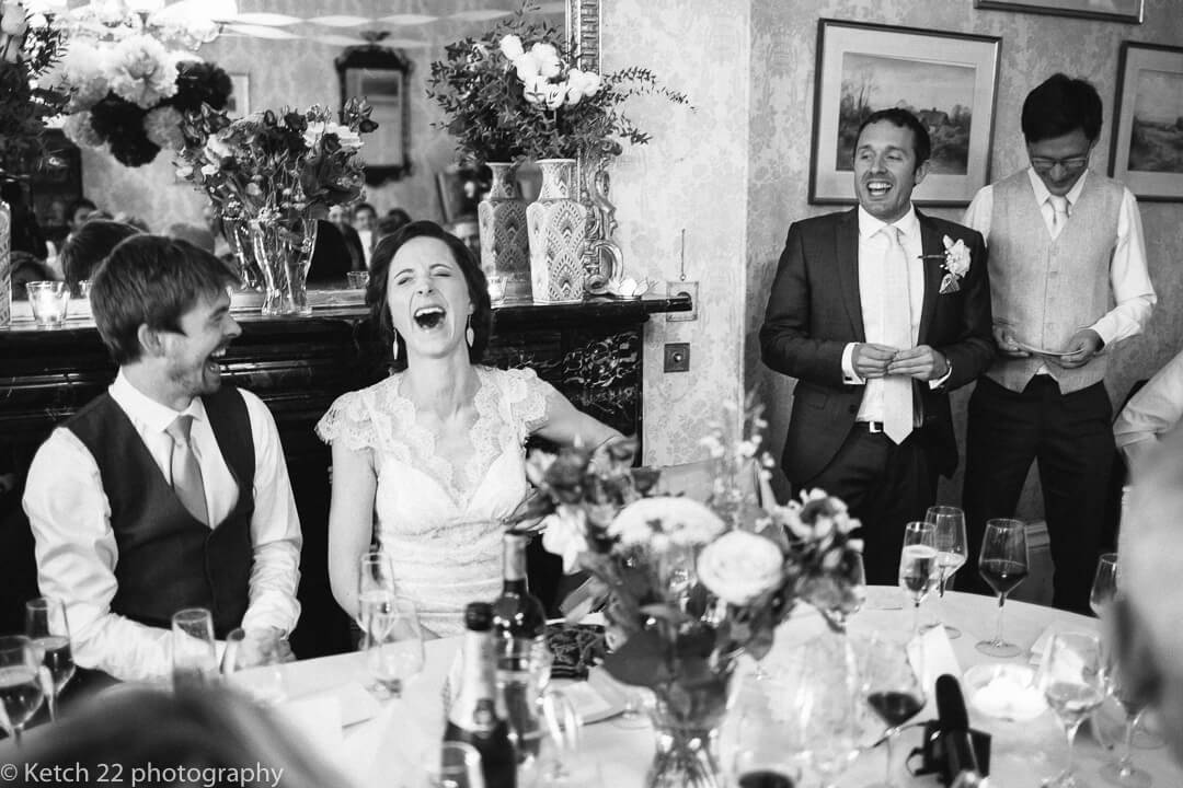 Expressive bride laughing out loud at wedding speeches