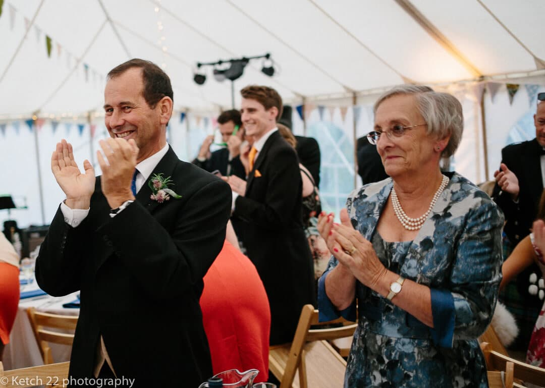 Wedding guests cheer bride and groom as they enter marquee
