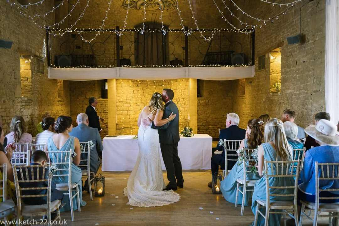 The first kiss at barn wedding ceremony