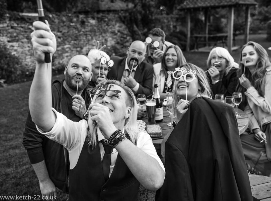 Black and white photo of wedding guests taking selfie