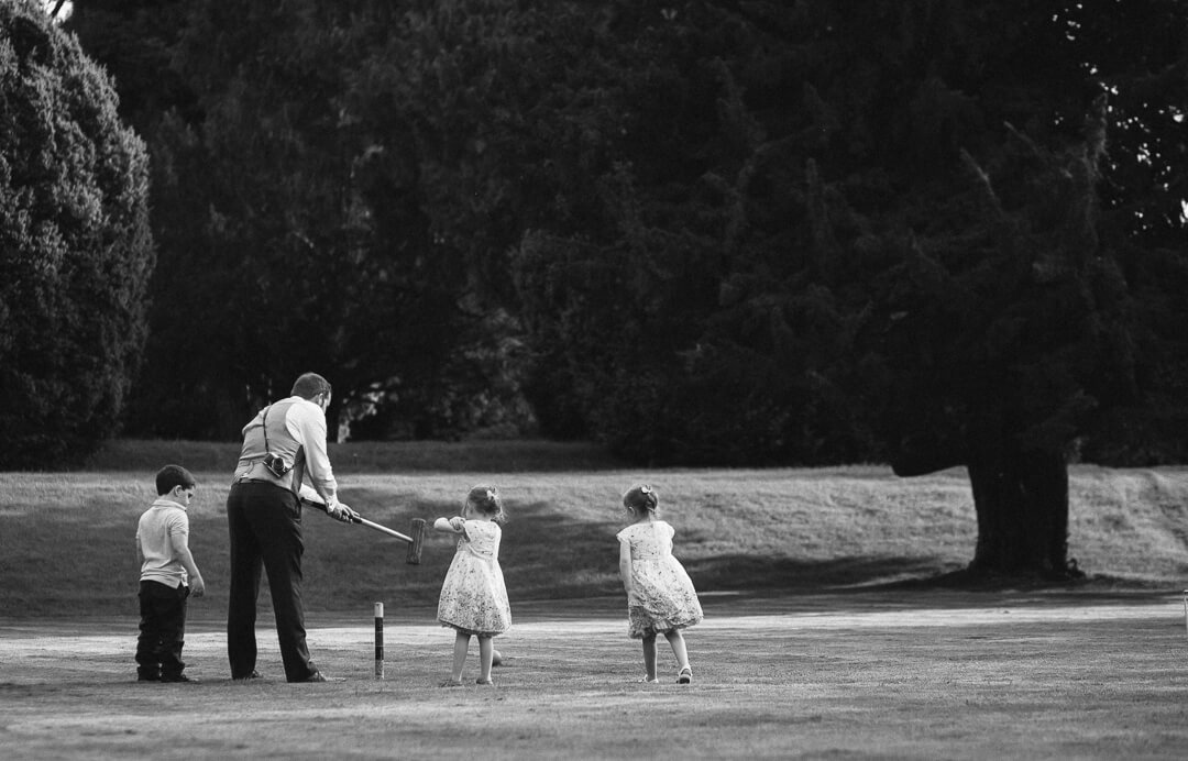 Dad and kids playing lawn games at wedding