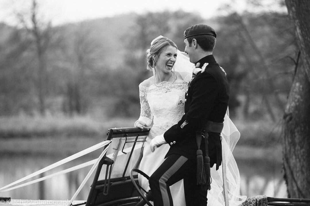 Portrait of bride and groom standing in Army jeep