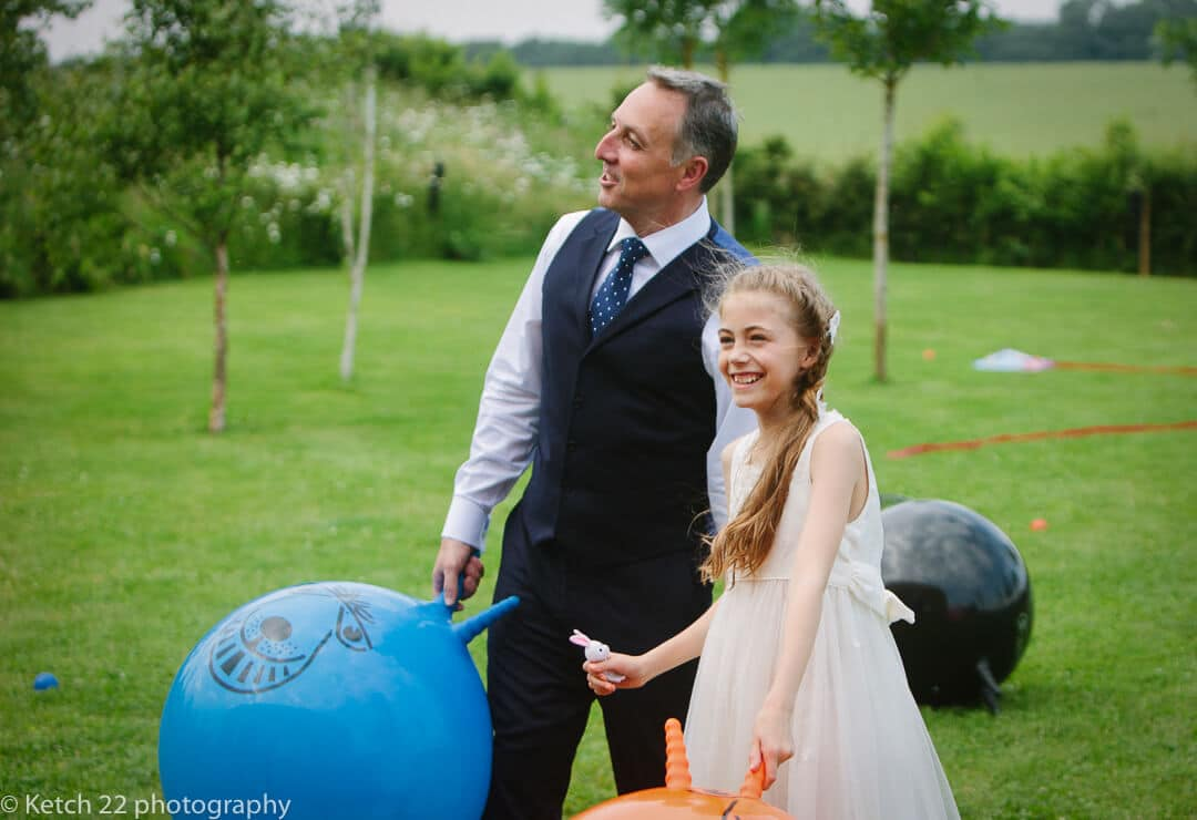 Groom and his daughter playing with space hoppers